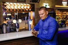 Mężczyzn spojrzenia w telefon za barem obraz stock