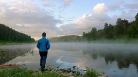 Mężczyzn stojaki na spokojnym brzeg rzekim z mgłą pod niebieskim niebem zdjęcie wideo