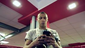 Mężczyzn stojaki w kącie pierścionek z bokserskimi rękawiczkami wokoło jego szyi trzymają telefon w jego rękach zdjęcie wideo