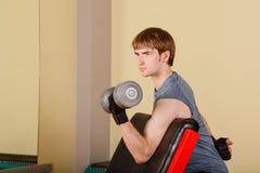 Mężczyzna ćwiczenia bicepsy z ręka ciężarami Obrazy Stock