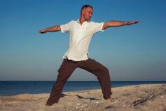 Mężczyzna ćwiczy joga na plaży zdjęcia stock