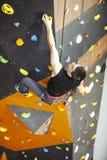 Mężczyzna ćwiczy pięcie na skały ścianie indoors Zdjęcia Royalty Free
