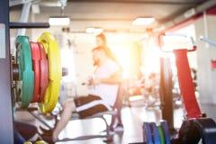 Mężczyzna ćwiczy symulanta w nowożytnym gym, pod nadzorem trenera, zmierzch błyszczy przez okno zdjęcia stock