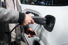 Mężczyzna ładuje electro samochód Mężczyzna mienie w ręki władzy kabla dostawie przygotowywającej czopujący wewnątrz w ładuje por zdjęcia stock