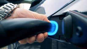 Mężczyzna ładuje elektrycznego pojazd Osoba trzyma ładowarki, stoi blisko elektrycznego samochodu zdjęcie wideo