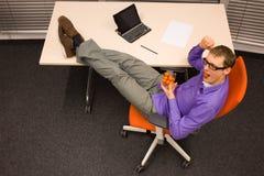 Mężczyzna łasowania hamburger w biurze - fast food Fotografia Royalty Free