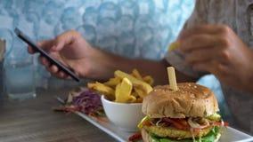 Mężczyzna łasowania hamburger z francuzów dłoniakami i gawędzenie na telefonie zbiory