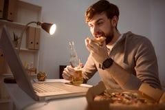 Mężczyzna łasowania pizza i patrzeć komputer zdjęcia royalty free