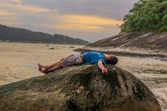 Mężczyzna łgarski puszek nad skałą zdjęcie stock