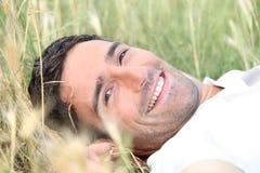 Mężczyzna łgarski puszek w polu Fotografia Stock