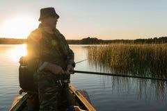Mężczyzna łowi od łodzi na zmierzchu Zdjęcie Royalty Free