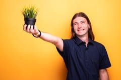 Mężczyzna śmia się podczas gdy pokazywać jego roślina garnek zdjęcie royalty free