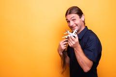 Mężczyzna śmia się podczas gdy trzymający zabawkarskiego samolot zdjęcie stock