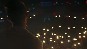 Mężczyzna śpiewa przed tłumem przy sceną zbiory