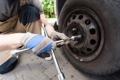 Mężczyzna śrubuje samochodowego koło Zdjęcie Royalty Free