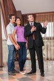 Mężczyzna agent nieruchomości pokazuje przytulenie pary nowego dom Zdjęcia Royalty Free