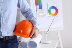 Mężczyzna architekt jest ubranym kostiumu mienia hełm, stoi w biurze obrazy royalty free