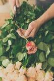 Mężczyzna asystent w kwiatu sklepu dostawie robi różanemu bukieta zbliżeniu Zdjęcie Stock