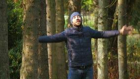 Mężczyzna atrakcyjna zewnętrzna pozycja w park rękach podnosić emocjonalnie, pojęcie świadomości sukces zbiory wideo