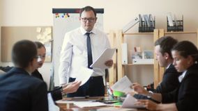 Mężczyzna Azjatycki pojawienie w garniturze mówi biznesowych kolegów o pracie robić, zbiera ich raporty dla zdjęcie wideo