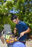 Mężczyzna barbecuing w jego ogródzie Zdjęcia Stock