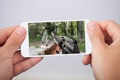Mężczyzna bawić się akci grę na smartphone Obrazy Stock