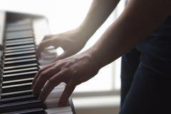 Mężczyzna bawić się fortepianową pozycję w domowym studiu obraz stock