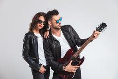 Mężczyzna bawić się gitarę elektryczną dla jego kobiety Obraz Stock