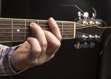 Mężczyzna bawić się gitarę, kciuki przemienia akordy fotografia stock