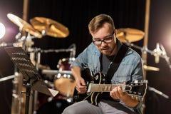 Mężczyzna bawić się gitarę przy pracownianą próbą Obraz Royalty Free