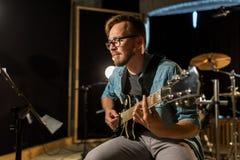 Mężczyzna bawić się gitarę przy pracownianą próbą Obrazy Royalty Free