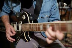 Mężczyzna bawić się gitarę przy pracownianą próbą Zdjęcia Stock