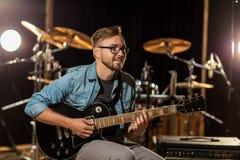 Mężczyzna bawić się gitarę przy pracownianą próbą Zdjęcia Royalty Free