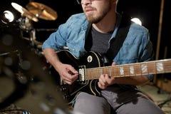 Mężczyzna bawić się gitarę przy pracownianą próbą Fotografia Royalty Free