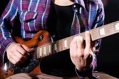 Mężczyzna bawić się gitarę w ciemnym pokoju Zdjęcia Royalty Free