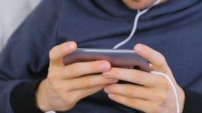 Mężczyzna bawić się grę w smartphone Gamer relaksuje R?ki zako?czenie zbiory