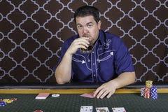 Mężczyzna bawić się grzebaka obsiadanie przy stołem zdjęcia royalty free