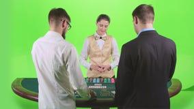 Mężczyzna bawić się grzebaka przy stołem handlowiec rozdają karty i układy scalonych zielony ekran swobodny ruch zbiory wideo