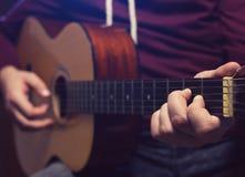 Mężczyzna bawić się muzykę przy drewnianą klasyczną gitarą Zdjęcia Royalty Free