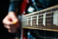 Mężczyzna bawić się na gitarze elektrycznej przeciw ciemnemu tłu obrazy royalty free