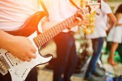 Mężczyzna bawić się na gitarze elektrycznej przeciw zespołowi obraz royalty free
