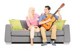 Mężczyzna bawić się na gitarze z jego dziewczyną Obraz Stock