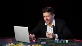 Mężczyzna bawić się online grzebaka przy stołem z bliska zdjęcie wideo