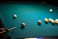 Mężczyzna bawić się Rosyjskich billiards ręka trzyma wskazówkę i piłkę na zielonym tle stół stawia piłkę wewnątrz obraz stock