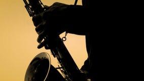 Mężczyzna bawić się saksofon w sylwetce. Zakończenie zbiory wideo