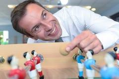 Mężczyzna bawić się stołową piłkę nożną podczas przerwa czasu fotografia royalty free