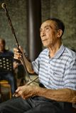 Mężczyzna bawić się tradycyjnego instrument muzycznego Chiny który dzwoni, brzmi jak skrzypce i, Erhu lub Nanhu Zdjęcie Stock