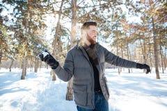 Mężczyzna bawić się z śniegiem w zima parku Zdjęcia Royalty Free