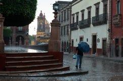 Mężczyzna bieg pod parasolem w historycznym centrum San Miguel De Allende w podeszczowej burzy zdjęcia royalty free