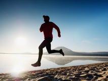 Mężczyzna bieg przy nadmorski zmierzchu czasem Biegacz atlety bieg przy nadmorski Sportowiec sprawności fizycznej sylwetka Zdjęcia Royalty Free